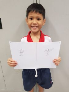 P1 student taking pride in their works while sharing the meaning of their drawing.