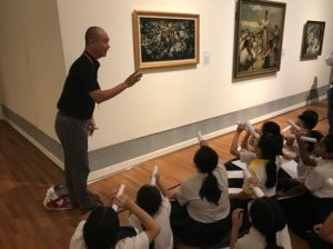 Students observing artworks from multiple perspectives.
